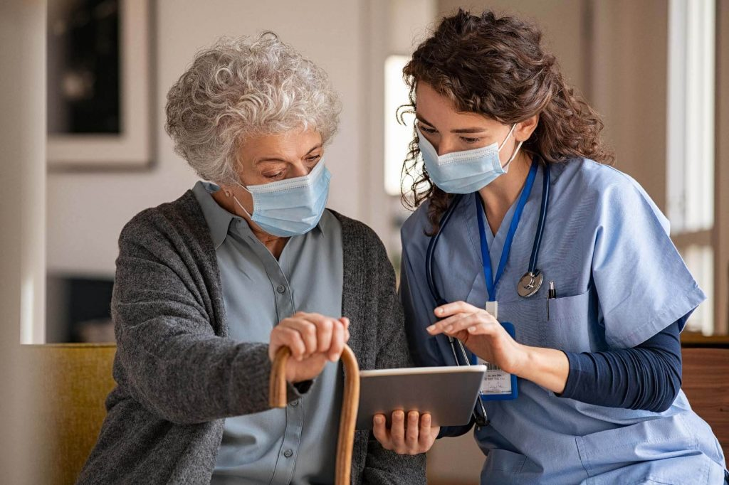 Nurse holding tablet computer talking to a patient