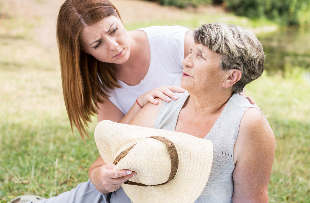 Concerned woman caring for a senior mom outdoors