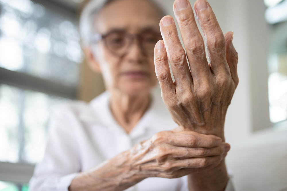 Elderly Woman Holding Her Wrist Showing Her Hand in Pain from Arthritis