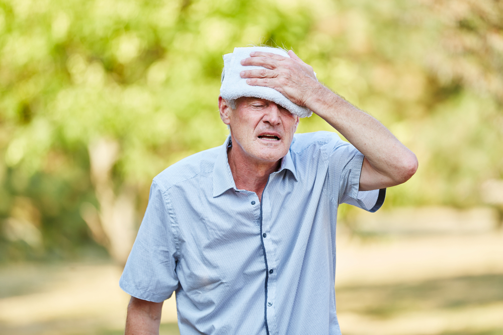 Man Cooling His Forehead With a Cold Towel