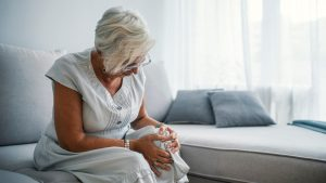 Senior Woman clutching her knee suffering from osteoarthritis